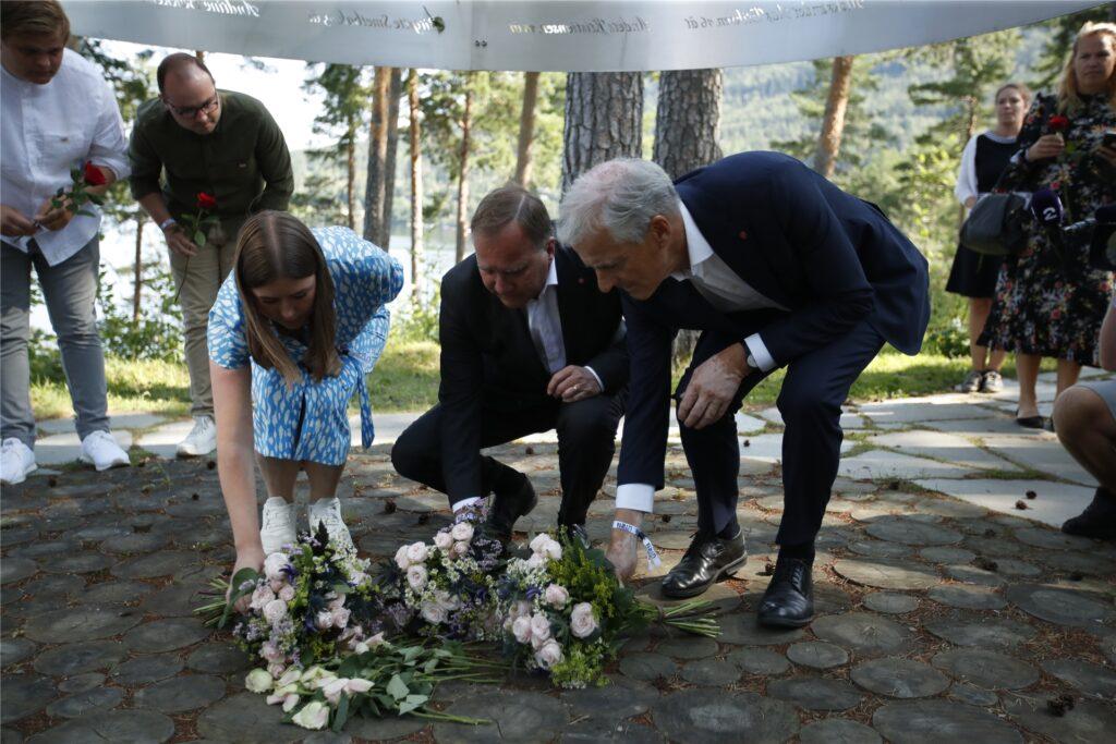 Astrid Hoem (l-r), Vorsitzende der AUF, Stefan Löfven, Ministerpräsident von Schweden, und Jonas Gahr Støre, Vorsitzender der norwegischen Arbeiterpartei, legen am Tag vor dem 10. Jahrestag des Terroranschlags am 22. Juli 2011 Blumen an der Gedenkstätte auf Utøya nieder.