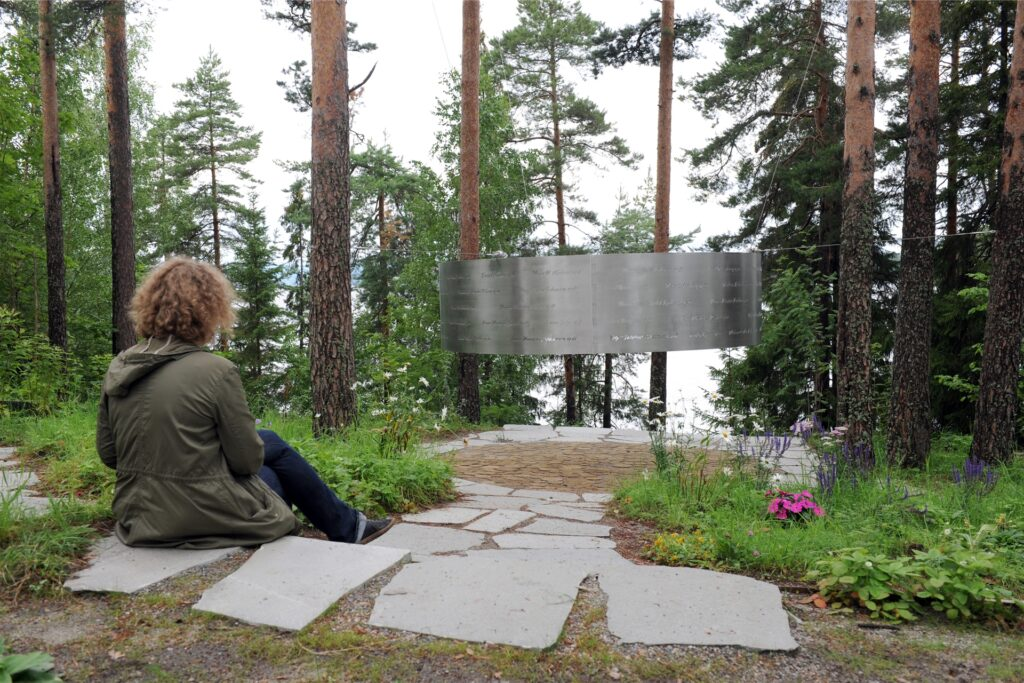 Eine Frau sitzt am 05.08.2015 auf der Insel Utøya (Norwegen) vor einem stählernen Ring, in den die Namen der Opfer der Terroranschläge eingraviert sind .