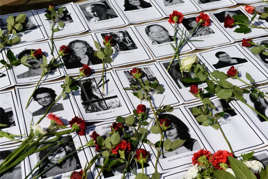 Rosen liegen vor den Nordischen Botschaften in Berlin auf Fotos der bei den Terroranschlägen in Norwegen am 22.07.2011 ermordeten Menschen.
